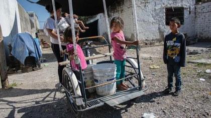 perla-sosa-con-sus-cuatro-hijos-y-el-triciclo-casero-que-usa-para-cargar-el-agua.jpg